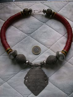 by Anne Marie | A large antique silver pendant from Persia. combined with  old small Yemeni silver beads, larger Tuareg metal beads, two gray sculpted clay beads from Mali (old spindle whorls) and red bakelite heishi from the African Trade.  | BeadArt Austria designs | SOLD