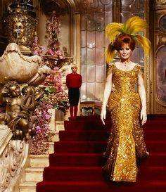 Hello, Dolly! 1969 The original design of the gold-beaded gown in the Harmonia Gardens scene weighed 40lbs and cost $8,000. Twice during rehearsals, she tripped over its 2.5-foot train. Other dancers also tripped over it during rehearsal. The train is shown intact when she starts down the stairs, but later disappears.