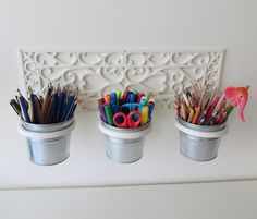 Organizing kids desk with wall mounted pot holder. It's a cast iron pot holder covered with acrylic paint.