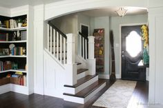 Living Room Remodel with yellow accents wood floors and built-in bookcases and columns with arches