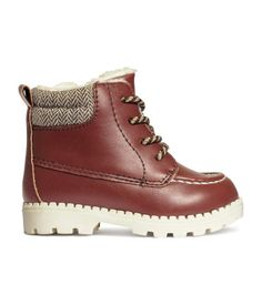 Size 4-5. Boots in imitation leather with moccasin seams. Lightly padded twill trim around top of leg, laces at top, and side zip. Chunky rubber soles. Pile lining.