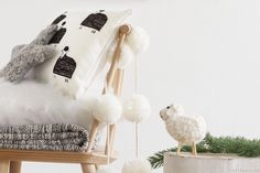 Ambiance déco laine pour Noël : boules blanches pompons, mouton de Noël, branche de sapin