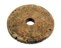 """Płaski krążek z poroża (XI-XII). Zachował się w całości. Dekoracja wykonana została za pomocą jednego elementu zdobniczego, mianowicie w całości złożona jest z """"oczek"""" (wykonanych cyrklem kółek). Krążek ten pełnił najprawdopodobniej funkcję pionka do rozpowszechnionej we wczesnym średniowieczu gry, zbliżonej do warcabów. Być może wykorzystywano go do gier w typie skandynawskim, w których pionki były pionowo przewiercane. Otwór po środku mógł pełnić funkcję zabezpieczającą lokalizację pionka…"""