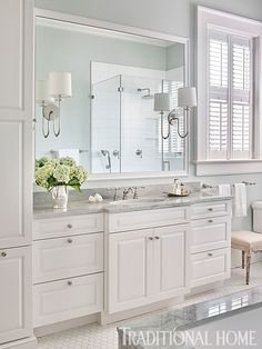 A hint of color on the pristine bathroom's walls coordinates with the marbling in the tub and countertop. - Photo: Emily Jenkins Followill / Design: Carolyn Griffith
