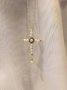 Understated and timeless.... This charming hand hammered gold wire cross pendant is wrapped with dainty, creamy freshwater pearls all along its length and width. The center pearl, is set against a gold-plated pewter spacer bead giving it star status. If youre a purist and understated