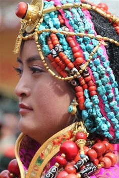 Government Celebrations in Kangding, Kardze, Tibet 2010 | A Khampa Tibetan girl in a traditional ceremonial costume from Palyul county. She wears the traditional women's headdress in Palyul with many strands of turqoise, and a gold necklace across her forehead, nine necklaces of coral and contemporary dzi, and coral and dzi beads set gold rings on six fingers. The costume and ornaments are probably the belongings of her family, and contain much of the family's wealth and savings.
