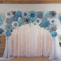 Love this backdrop idea.  Sheer curtains with white lights and an array of paper flowers.