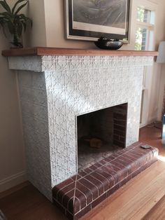 Pressed metal panels used to decorate this free-standing fireplace ...