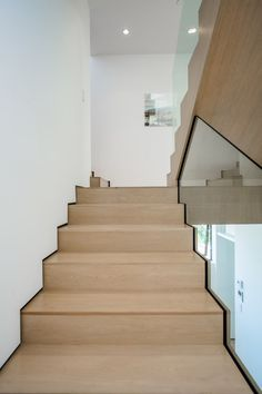 Light wood stairs have been paired with white walls and glass for a contemporary…