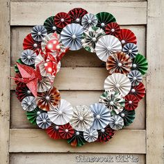 """Another of our 14"""" folded pinwheel rosette wreaths with paper cranes in the custom order for a Japanese restaurant. Red and green Japanese themed paper with pearl embellishments. #glascockgifts #origami #paper #paperart #wreath #paperwreath #walldecor #handmade #christmaswreath #christmas #japan #papercranes"""