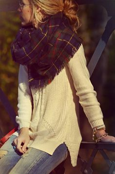 Large knit white sweater, casual jeans, and an oversized tartan scarf.