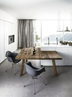 Belle association du bois presque brut avec des meubles laqués et un sol en béton