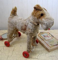 Adorable antique toy dog on wheels.