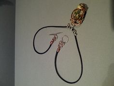Silver and copper wrapped pebble on thong