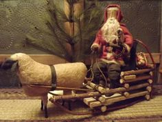 Prim Santa...with twiggy sleigh...pulled by a grungy sheep...pine tree...old punched tin cupboard.