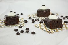 Fudgy Truffle Brownies with Espresso decorated with whipped cream and garnished with a chocolate covered espresso bean displayed randomly with chocolate espresso beans.