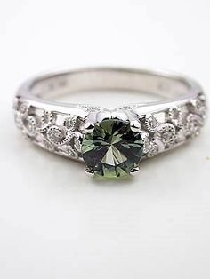 Green Sapphire ring. Green sapphire set in a delicate vine of diamonds, representing the hope and renewal of spring. I love it.