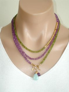 www.etsy.com/...?    Ashira Pink Lavender Amethyst and Green Peridot Gemstone Necklace with Charms. $440.00, via Etsy.