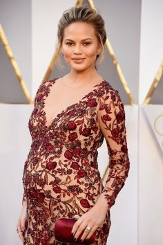 Chrissy Teigen embracing her curves in a form-fitting lace gown from Marchesa at the 2016 Oscars. While an empire waist always flatters, the deep and angular neckline enhances the rest of the look's feminine lines.