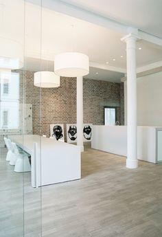 Parquet clair et mur de briques à envisager sur un espace de travail. Lumineux, convivial et design.