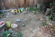 dry river bed with stumps for seating, trucks, buckets and plastic animals