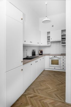White kitchen with herringbone flooring in a 1st district Budapest luxury apartment designed by Andras V. Lestak, photography by David Kovacs