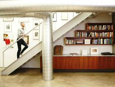 I generally like exposed utilities, but this is a bit much IMHO.  However, I do like those built-ins under the stairs.  Great console and bookshelves!