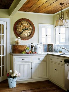 kitchen love the big clock, old light, white cabinets, solid wood ceiling....what a perfect cottage kitchen