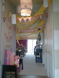 "I printed Little Misses logo in purple on plan white paper to make lanterns for the entrance. I cut 12"" stripes of yellow plastic table cloth from the dollar tree, stapled the ends together and draped from the ceiling to look like Rapunzel's hair. Tangled Party. {pinkinkdoodle}"