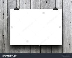Close-up of one horizontal paper sheet with clips on vertical wooden boards background
