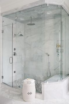 An angled seamless glass shower is clad in large gray marble staggered tiles on ceiling and wall accented with three shower heads alongside a gray mosaic marble shower floor.