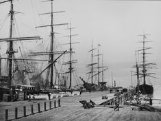 """On the wharves, San Francisco, 1900."" Moored schooners' masts form a wall around the dock. By Henry G. Peabody"