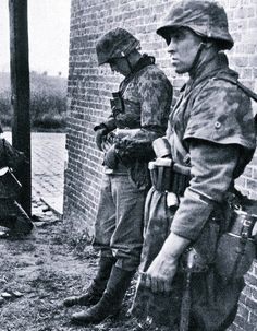 Taking a breather. Both men wear the short camouflage smock and helmet cover, both standard issue for the Waffen SS.