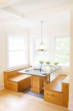 The oak columns under the sturdy dining nook table match the benches on either side. Storage is plentiful with pull-out racks behind the slim doors and full-length drawers in each storage bench.