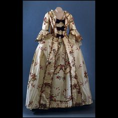 Robe à la francaise, England (Spitalfields), worn in Virginia, c. 1750, c. 1770 gown. Ivory silk lustring taffeta with brocaded floral bouquets in reds, rose, purple, blues, yellow, greens entertwined with ivory weft-float pattern of trailing vine and purple cone-like flowers.