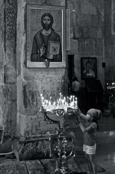 "2nd Place, Local Culture and Life: Frank Miller, Georgia  ""During a trip to Mtskheta, we visited the Svetitskhoveli Cathedral. Georgian history and culture is inextricably linked to Orthodox Christianity. Here, a Georgian girl lights a candle in prayer before an icon of Christ."""