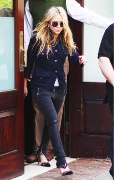 Ashley Olsen wears a blue fitted textured jacket, skinny cargo pants, and round frames.