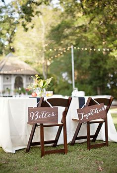 Brides.com: . Pretty wooden signs complement this romantic outdoor reception space.