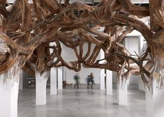 photograph by André Morin Designed by Henrique Oliveira to look like an impossibly tangled Gordian Knot, the Baitogogo sculpture is installed within an exhibition space at Palais de Tokyo as a mass of tree-like plywood branches.