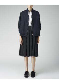 Varsity Jacket by Comme Comme.  A reinterpreted classic; varsity jacket done in a lightweight gabardine with an exaggerated, wide drawstring hemline. Worn with / Comme Comme Patch Shirt, Comme Comme Suspender Dress & Simone Rocha Velvet Bow Loafer.