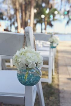 Globe jars filled with turquoise stones and hydrangeas for a beach themed party (different stones for a peach, gold and white color scheme)