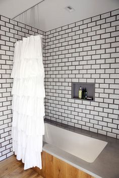 Bathroom...white tile & dark grey grout with concrete surround and wood floors.