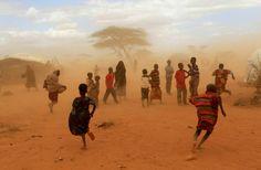Somalis na poeira do campo de refugiados de Dadaab, condado de Mandera, Quênia. Aqui os efeitos do aquecimento global são catastróficos. A seca aumentou de duração, e o rio Dawa, um rio intermitente que secava 2 meses por ano, hoje fica seco por 4 meses. Pasto para os animais está cada vez mais longe, fome e desnutrição se alastram.  Thomas Mukoya…