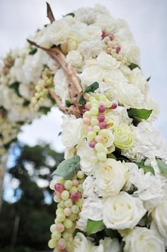 Green and red grapes add a touch of color to an altar made of white roses and hydrangeas.