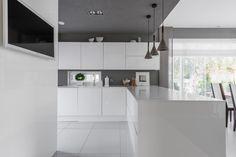 Tyylikäs valkoinen keittiö avautuu avaraan ruokailutilaan ja olohuoneeseen. Kauniit riippuvalaisimet kruunaavat kokonaisuuden.