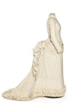 Robe de mariée portée par Adelina Eberhardt pour son mariage le 11 novembre 1882, avec M. Louis Blondeau, au temple de la rue Roquepine, Paris, 8ème arrondissement.  Matières et techniques :     Satin de laine ivoire  Mesures :     longueur devant (en cm) : 140  longueur dos (en cm) : 190  carrure dos (en cm) : 34  tour de poitrine (en cm) : 80  tour de taille (en cm) : 60