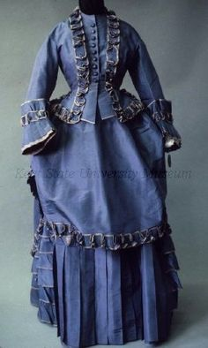 1870 Day Dress Culture: French Medium: silk taffeta Lapis blue silk taffeta day dress. The bodice with high round neck and buttons down center, trimmed around neck, down the front, peplum and at cuffs with ruffle of same silk edged with grey silk. The skirt with vertical pleats at the front and same blue and grey tiered ruffles at the back. The separate overskirt with bustle and dipped hem edged with same blue and grey ruffle.