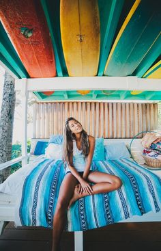Mexican blanket, surfboards stored and on display, bright colors anchored with white frames.