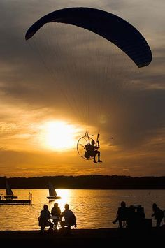 A man flying a powered paraglider passes the Union Terrace.