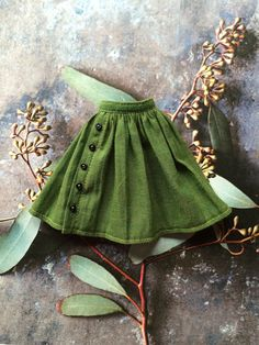 This pretty skirt is made from a gorgeous green shot cotton with delicate buttons. It fastens with a snap at the back. NB. This item will be